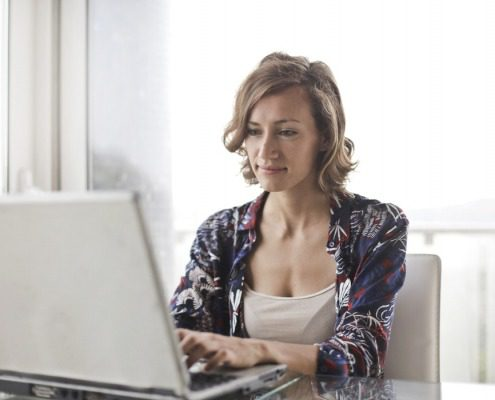 Self employed woman, smiling filling in her pay stub generator templates on a laptop